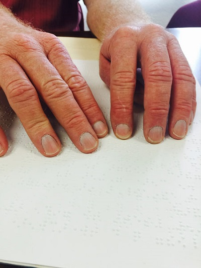 reading Braille dots with fingers on the page