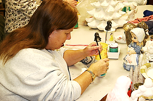 a UCB member is painting a ceramic figure